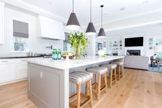 Modern Farmhouse bright white kitchen with a carrara marble oversized island. The gray on the island is Galveston Gray by Benjamin Moore Project Newport Harbor - Blackband Design