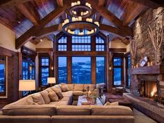 I love everything about this room. The high ceiling, exposed wood beams, the stone fireplace. Love it !!