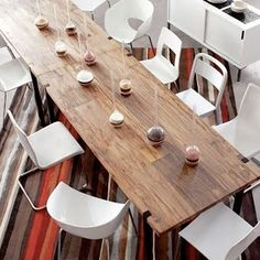 Rustic dining table with modern white chairs.