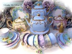 A tealight display of vintage blue, soft green and gilded lilac teapots. Paired with matching vintage teacups and tea sets.