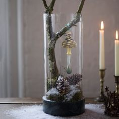 The winter forest comes to life inside a sleek glass hurricane with a marble base. Against a backdrop of fresh moss and faux snow, a glittering mushro