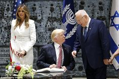 First Lady Melania Trump (left) and Israel's President Reuven Rivlin (right) stood next to Donald Trump as he signed the guest book at the President's Residence in Jerusalem