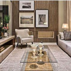 Sala de estar com parede revestida em madeira, quadros compondo o ambiente e poltrona na cor creme/bege. Mesa de centro em vidro, sofá e painel de tv.