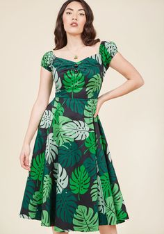 <p>You're pleased as punch over this off-the-shoulder dress and you want to party about it! Style the sultry black hue - printed with shades-of-green tropical leaves - neckline pleating, and decorative buttons of this cotton midi with a daytime look and post up in the park in sweet celebration.</p>