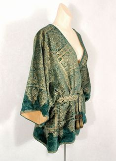 Fortuny stenciled velvet short jacket, c.1930. The pattern is hand stenciled in many layers of subtly changing gold pigment, reproducing the Renaissance fresco effect. The ground cloth of teal silk velvet drapes beautifully. The jacket is totally lined with apricot silk faille. The belt ends are finished with metallic bronze tassels. Sideway