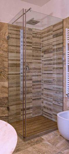 Mosaico in travertino modello Bars nel rivestimento di questa doccia