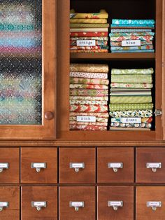 In the Bank... Stacks of pretty quilting fabrics are sorted and identified by color using shelf labels. Eighteen spice drawers house notions and supplies. Designed to hold labels, the drawer pulls ensure that everything is easily found and returned to the proper place.