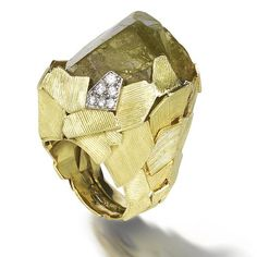 A dress ring, by Andrew GRIMA, 1971/2  The pale green beryl crystal surrounded by a series of abstract 18 carat gold textured plates forming the mount and shank, signed Grima, London hallmark (hva)