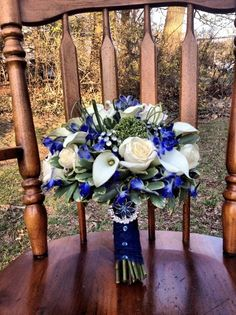 Ivory roses, ivory miniature calla lilies and royal blue delphinium, accented with rhinestones by trojansoccerplayer5@gmail.com
