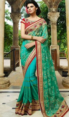 This green and turquoise color shade georgette net sari is adding interesting glamorous showing feel of cute and graceful. This pretty attire is displaying some unbelievable embroidery done with bead, lace, resham and stones work. #stoneworksaree #reshamworksaris #floraldesignsari