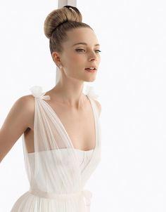 Bride with big ballerina bun and tulle tied wedding dress over a corset style bodice @myweddingdotcom