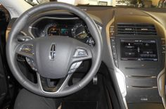 """The 2014 Lincoln MKZ steering column is different. Departing from the conventional, designers put the transmission controls in a vertical series of ergonomic buttons on the center instrument panel. For even sportier operation, press the """"S"""" button* and use the paddle shifters on the steering wheel. Eliminating the floor shifter frees up space between the driver and passenger seats, and enhances the clean, uncluttered appearance that characterizes the whole of the interior."""