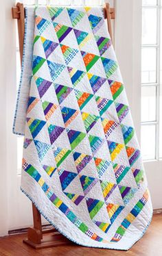 Combine colorful strips of fabric with a crisp white to make this cheery pyramid block quilt.