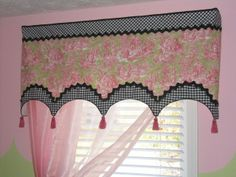 Flat board mounted shaped valance with contrasting banding on top and bottom with solid gimp to separate the fabrics. Tassels added to complete the look.