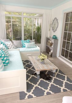 An adorable turquoise and gray sun room with wood coffee table and shelf