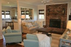 love the brick fireplace, wicker shades, white kitchen and wood floors!