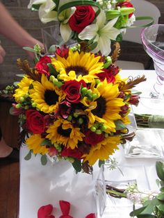 I think sunflowers look great paired with deep fall colors like reds, oranges, and purples. This bouquet looks wonderful! Red roses and sunflowers.