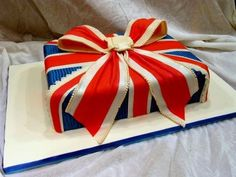 Union Jack cake - Birthday cake for a friend who was moving to England. Inspired by a retro Union Jack cushion I once saw, thinking it would make a great cake! The cake is covered in fondant with a gum paste bow, details are all fondant. British Cake, British Sweets, British Party, Union Jack Cake, Union Jack Cushions, London Party, British Things, Grad Parties, Fancy Cakes