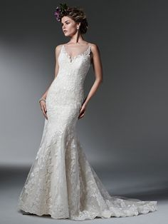 Sottero and Midgley - SILVIA, Elegant and understated, this chic fit and flare wedding dress is accented with bold floral lace appliqués adorning the bodice and edging a deep V illusion neckline. Finished with a plunging, illusion back and covered buttons over zipper closure.