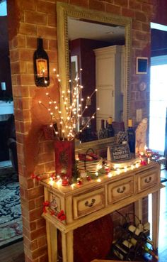 Faux brick wall room divider. Distressed console table. Faux Verdigris finished mirror. Adorned for the holidays.