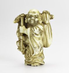 Netsuke of carved ivory, Hotei standing with a stick over his shoulder with a bundle at one end and a child at the other, unsigned: Japan