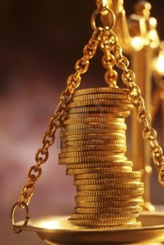 stacks of bright new shiny gold coins placed on weighing scales Stock Photo