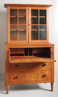 DESK AND BOOKCASE. Probably Midwestern, ca. 1820 -1840. Well-figured curly maple with cherry interior. Poplar secondary. Rich color with mellow finish. Three-drawer base with panel sides, turned front feet and inside taper on the rear feet. Bookcase has two fixed shelves behind four paned doors.