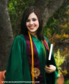 Cap and  gown high school portrait of girl holding a book. Photo was taken outdoor.