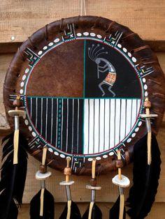 Très bel objet - Pièce Unique - origine du territoire Navajo (Arizona) peinture sur rawhide (cette peau sous la fourrure qui sert également à fabriquer les tambours) motifs géométriques et Kokopelli plumes noires, rondelles os diamètre 34 cms hauteur totale 60 cms  Pièce issue de ma collection personnelle.  À lorigine, les shamans utilisaient le bouclier de protection comme instrument de guérison. Aujourdhui, sa symbolique est importante pour nous rappeler limportance de léquilibre dans…