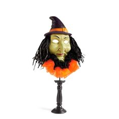 Relive the magic of Halloweens past with our vintage-inspired Witch Halloween Mask on Pedestal. So frightfully fun and colorful, she deserves prominent    placement on your mantel, or any tabletop, for all partygoers to see. Based on original designs, witch features a purple hat accented with an orange band.    Detailed and expressive face is a ghastly green, and hair made from raffia and fabric embellishments bring the entire piece to life. Take turns having your    picture taken, disgu...