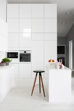 High gloss white kitchen with Island and high mural cabinets | Interior designer Laura Seppänen