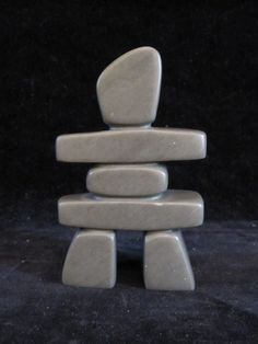 Inuit soapstone carving signed, Simonie Iqaluq depicting an Inukshuk. With original paper label.