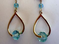 Twisted bale earrings in silver tone, holding aquamarine rondells with silver tone leverbacks. $18.00