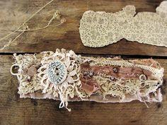 Dust of ages - salvage textile wristcuff - vintage lace - ceramic button detail. $65.00, via Etsy.