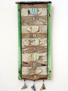 Shirley Vauvelle, Mixed Media Artist / selection of hand built fishes and vintage numbers from 1940's newspapers. (earthernware, driftwood, collage, 38cm x 20cm)