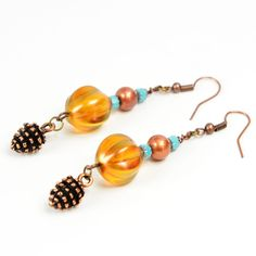 You'll be pretty as a pinecone wearing these playful copper drop earrings. Each two-inch drop earring features turquoise Czech cathedral beads, an iridescent bronze Indian glass bead and a large (12mm) translucent copper Czech melon bead. A copper-plated pewter charm completes the look. Ear wires are copper.  The Smallest Planet Guarantee  All Smallest Planet jewelry is handmade by me, Sara Kelly, in my home studio in San Diego, California. As a one-person shop, I take great pride in my w...