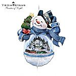 """Thomas Kinkade Snowman Victorian Christmas Ornament: Bringing Holiday Cheer. Outside, he's a jolly snowman decked out in a snappy top hat. But look through his clear outer """"shell"""" to discover Victorian Christmas artwork from the Painter of Light™! The holidays take a festive turn with this collectible Thomas Kinkade Snowman Christmas ornament, a first-ever exclusively from The Bradford Exchange to feature a moving train and a charming village sculpture from the most collected artist of our…"""