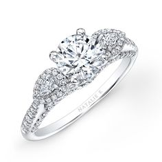 Natalie K - Two pear shaped side stones surrounded delicately by brilliant round white diamonds sit on either side of a center mounting and sit prong-set on the shank in this beautiful diamond engagement ring.