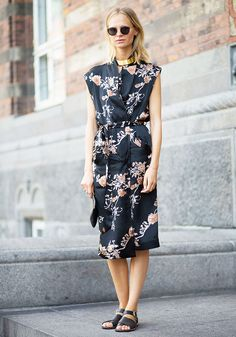 A floral wrap dress is worn with a statement gold choker, round sunglasses, and black sandals
