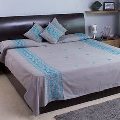 Give your bed a tasteful makeover with this elegant grey cotton bed cover with blue hand embroidery work.