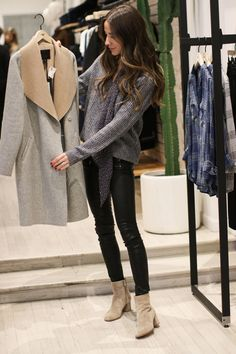 Something Navy wearing the Richelle Sweater, Edgemont in Black Leather, and Floral Skinny Scarf, holding the Lily Coat.