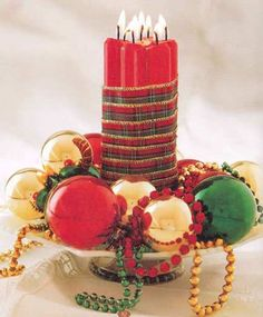 Christmas centerpiece made by wrapping a bundle of candles in festive ribbon. Place on a stand and surround with Christmas ornaments and beads.