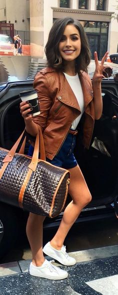 Who made Olivia Culpo's white sneakers, brown bag, tee, leather jacket, and blue shorts? - Street Fashion