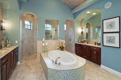 Arched doorways lead to a walk-in shower with high windows behind this tiled tub. One of eight new homes in The Preserve by Jimmy Jacobs Custom Homes in Georgetown, Texas.