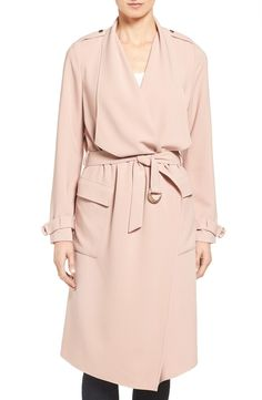 Swooning over this classic trench coat with a modern twist. A wide, draping collar and pale pink tone define this gorgeous must-have while belted cuffs, spacious pockets and a tie belt add a timeless touch.