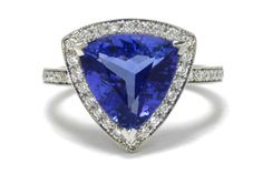 The Schiavone Ring. Taking center stage is a velvety violet-blue triangle cut Tanzanite of 3.60 carats, surrounded by a glimmering diamond halo and band. You'll love the cool angles and cut of the gem and the delicate millegrain around the border. It includes its American International Gemologists Report.