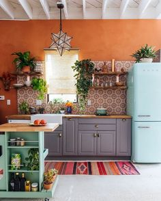 Colorful Moroccan inspired kitchen interior dream house kitchen orange walls eclectic cozy artsy rug blue retro fridge center island aqua mint green #kitcheninterior
