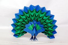Origami peacock with fanned tail, made from one piece of uncut two-colored paper.
