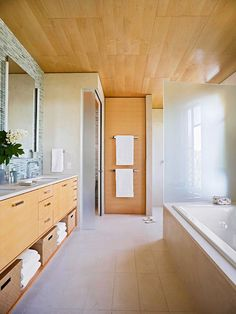 Create a degree of separation between the doorless shower and other bathroom fixtures. Tempered-glass partitions signify a transition between the vanity and tub area and a commode closet on the left while providing privacy to the doorless walk-in shower on the right. A wide doorway allows easy access to the shower room, which is set apart from the main room by a short step down and a shift in flooring material.