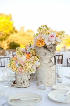 Rustic Wedding Decor.  Tree trunk flower vases.  Love the flower colors also